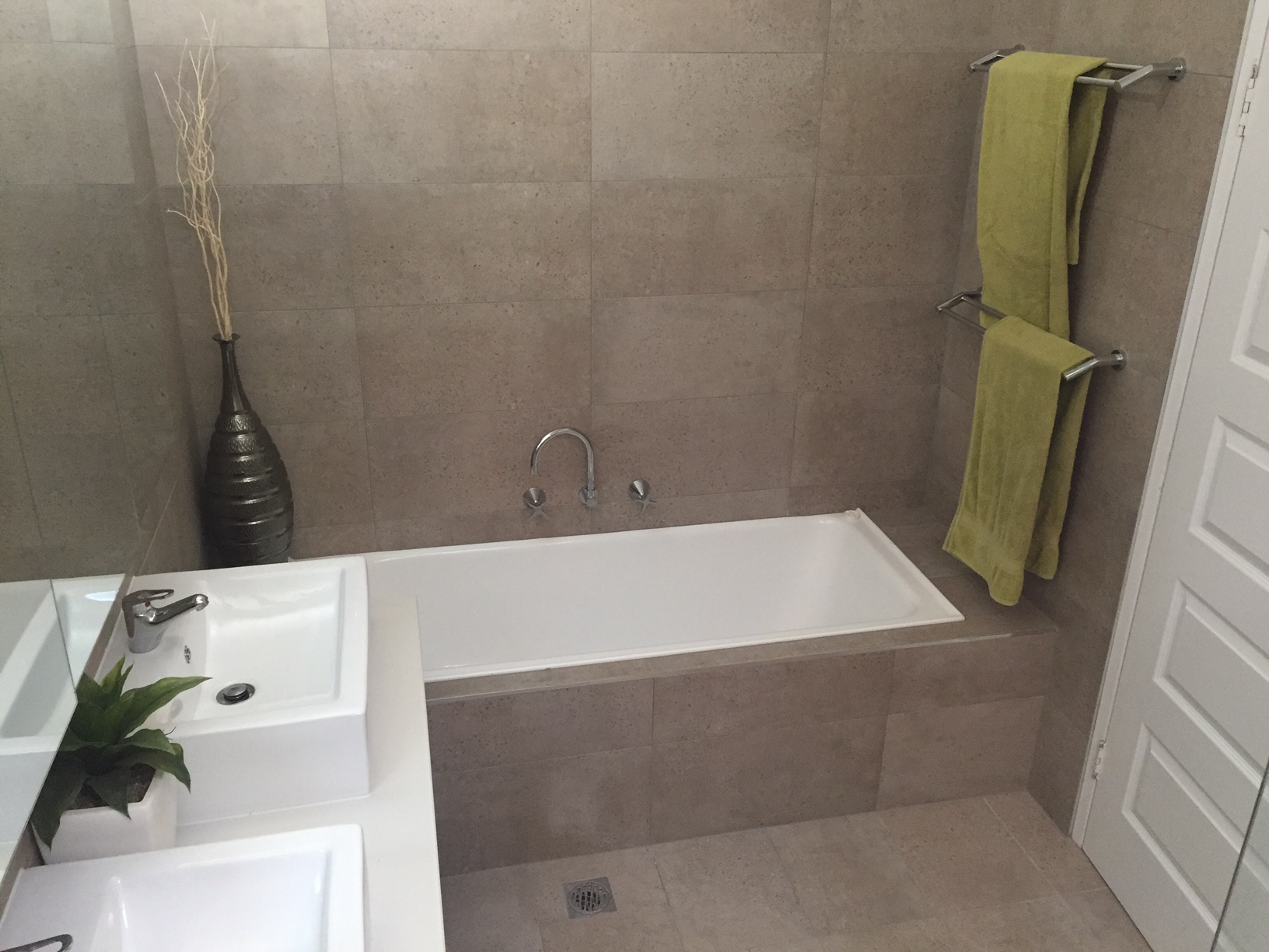 Natural stone look tiles, highlighted with white vanity and bath